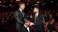 Bintang Real Madrid, Cristiano Ronaldo, berbincang dengan striker Barcelona, Lionel Messi, saat acara penghargaan pemain terbaik FIFA 2017 di London, Senin (23/10/2017). Cristiano Ronaldo berhasil meraih pemain terbaik FIFA 2017. (AFP/Ben Stansall)