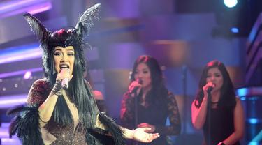 """Dengan rambut terurau dan hiasan kepala bewarna hitam yang nampak seperti tanduk, Titi DJ menyanyi dalam konser """"A Night with Judika"""" di Studio Sepat, Jakarta pada tahun 2015 silam. (Kapanlagi/Bambang E Ros)"""