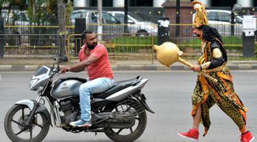 """Seorang seniman berpakaian seperti """"Yamaraj"""" (R), dewa kematian Hindu, berjalan mengejar pengendara motor tanpa helm sebagai bagian kampanye 'Road Safety Week' yang diselenggarakan oleh polisi lalu lintas di Bangalore (10/7). (AFP Photo/Manjunath Kiran)"""