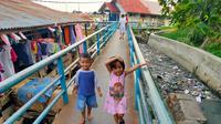 Anak-anak bermain dengan girang meskipun aroma busuk dari sampah yang menggenang di Sungai Tawar, anak Sungai Musi Palembang ini mengganggu pernapasan (Liputan6.com / Nefri Inge)