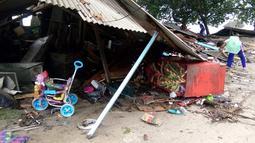 Seorang pria mencari barang-barang dari rumahnya yang rusak setelah tsunami menerjang Pantai Carita, di perairan Banten, Minggu (23/12). Data sementara jumlah korban dari bencana tsunami di Selat Sunda tercatat 43 orang meninggal dunia. (SEMI / AFP)