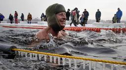 Seorang peserta tersenyum saat mengikuti kompetisi renang di perairan es di sungai Neva selama Big Neva Cup of Ice Swimming di St.Petersburg, Rusia, (4/3). (AP Photo/Dmitri Lovetsky)