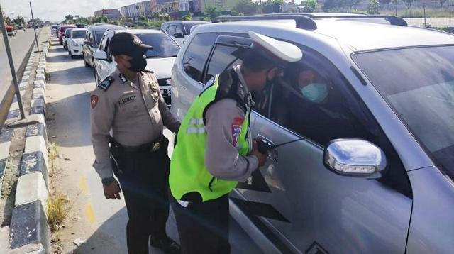Personel Polresta Pekanbaru memeriksa kendaraan di pos penyekatan larangan mudik. (Liputan6.com/M Syukur)