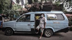 Pakde (52), sopir mikrolet M01 rute Pasar Senen-Kampung Melayu berpose di Kramat Pulo, Senen, Jakarta Pusat, Selasa (22/6/2021). Mobil angkot jenis mikrolet ini bukan tengah parkir di terminal menunggu penumpang, melainkan bersiap mengantarkan pengamen ondel-ondel. (merdeka.com/Iqbal S. Nugroho)