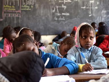Murid menulis di buku saat menghadiri kelas di sekolah dasar di Pikine, Dakar, (30/1). Pendidikan di Senegal menjadi prioritas saat konferensi ketiga tentang pemulihan dana Kemitraan Global untuk Pendidikan (GPE) mulai 1 Februari 2018. (AFP Photo/Seyllou)