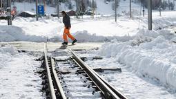 Seorang petugas memeriksa kondisi rel kereta api yang tertutup salju tebal di salah satu resor ski paling populer di Swiss (10/1). Sekitar 13.000 wisatawan terjebak akibat bencana tersebut. (AFP Photo/Fabrice Coffrini)