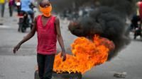 Seorang bocah lelaki meneriakkan slogan-slogan anti-tentara ketika para polisi yang tidak bertugas memprotes gaji dan kondisi kerja, di Port-au-Prince, Haiti, Senin 24 Februari 2020. (AP Photo/Dieu Nalio Chery)