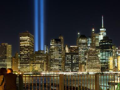 Sepasang kekasih menikmati 'Tribute in Light' dari sisi Brooklyn Promenade untuk mengenang tragedi serangan WTC di New York, Minggu (10/9). Kota New York memperingati 16 tahun tragedi serangan bom pada 11 September 2001 silam. (AP Photo/Mark Lennihan)