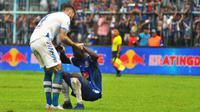 Bek Persib Bandung, Bojan Malisic membantu gelandang Arema, Makan Konate untuk bangkit usai pertandingan di Stadion Kanjuruhan, Kab. Malang, Jumat (22/2/2019). (Bola.com/Iwan Setiawan)