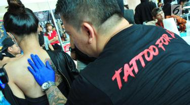 Seniman bersiap mentato punggung seorang wanita saat mengikuti lomba tato di Jakarta, Sabtu (23/9). Event tato terbesar Se-Jakarta ini sudah ke empat kalinya di adakan. (Liputan6.com/Helmi Afandi)
