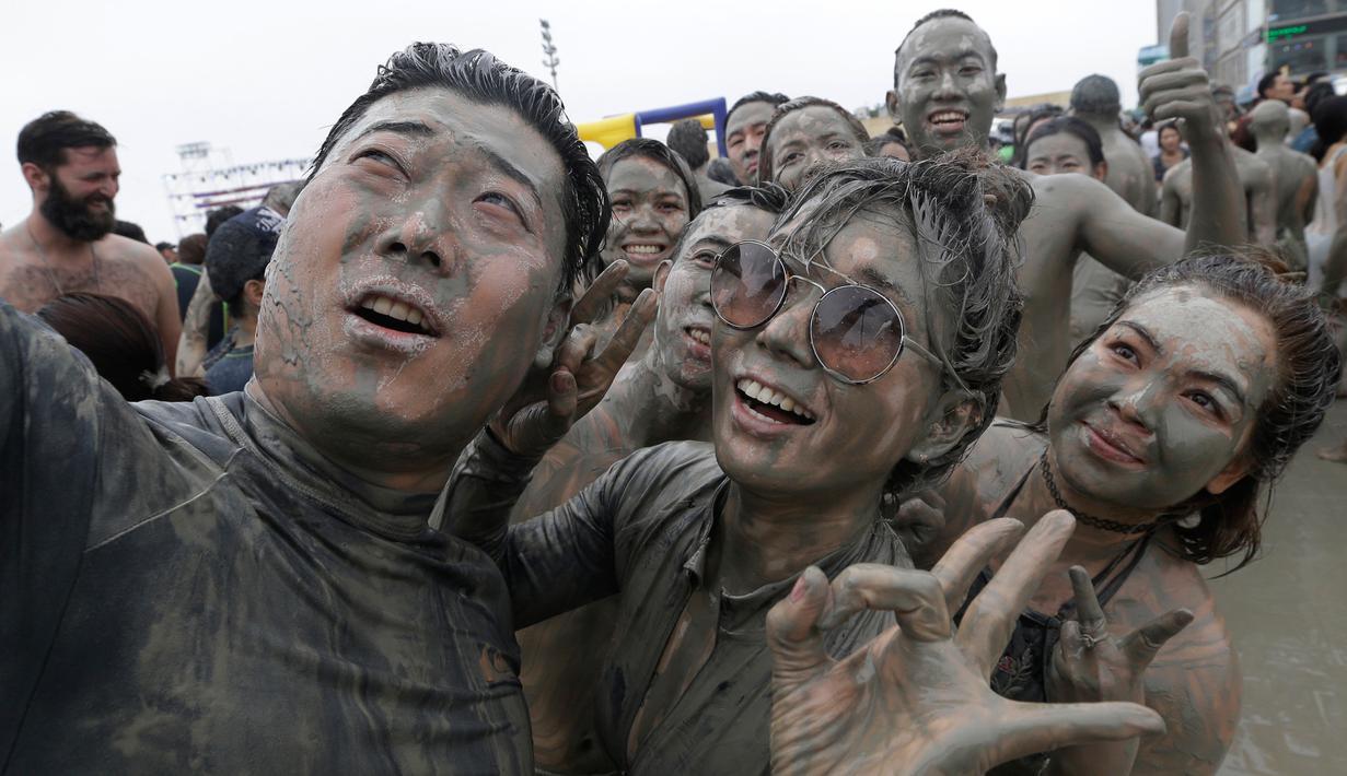 Warga berselfie selama Festival Lumpur Boryeong di Pantai Daecheon di Boryeong, Korea Selatan, (22/7). Festival lumpur tahunan ke-20 ini selalu mengadakan berbagai perlombaan yang menggunakan arena berlumpur. (AP Photo/Ahn Young-joon)