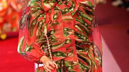 Seorang model berpose di atas catwalk dengan membawa tas besar mirip tas pasar dan mengisinya dengan sayuran untuk koleksi Dolce & Gabbana Spring/Summer 2018 di Milan Fashion Week, Minggu (24/9). (AFP PHOTO / Andreas SOLARO)