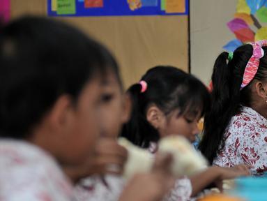 Siswi menyantap makanan tambahan saat program Penyediaan Makanan Tambahan Anak Sekolah (PMTAS) di SD Negeri 01 Tanjung Priok, Jakarta, Kamis (28/3). Pemprov DKI Jakarta menggelontorkan dana Rp 324 miliar untuk memenuhi gizi anak SDN di Jakarta dengan program PMTAS. (merdeka.com/Iqbal S. Nugroho)