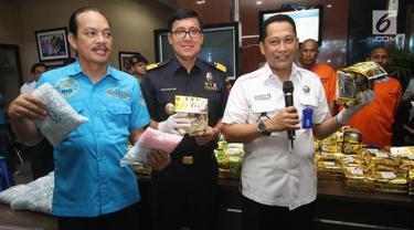 Kepala Badan Narkotika Nasional (BNN) Komjen Pol Budi Waseso (kanan) bersama Direktur Informasi Kepabeanan dan Cukai DJBC Bahaduri Wijayanta (tengah) menunjukan barang bukti penyelundupan narkotika di Jakarta, Rabu (27/9). (Liputan6.com/Immanuel Antonius)