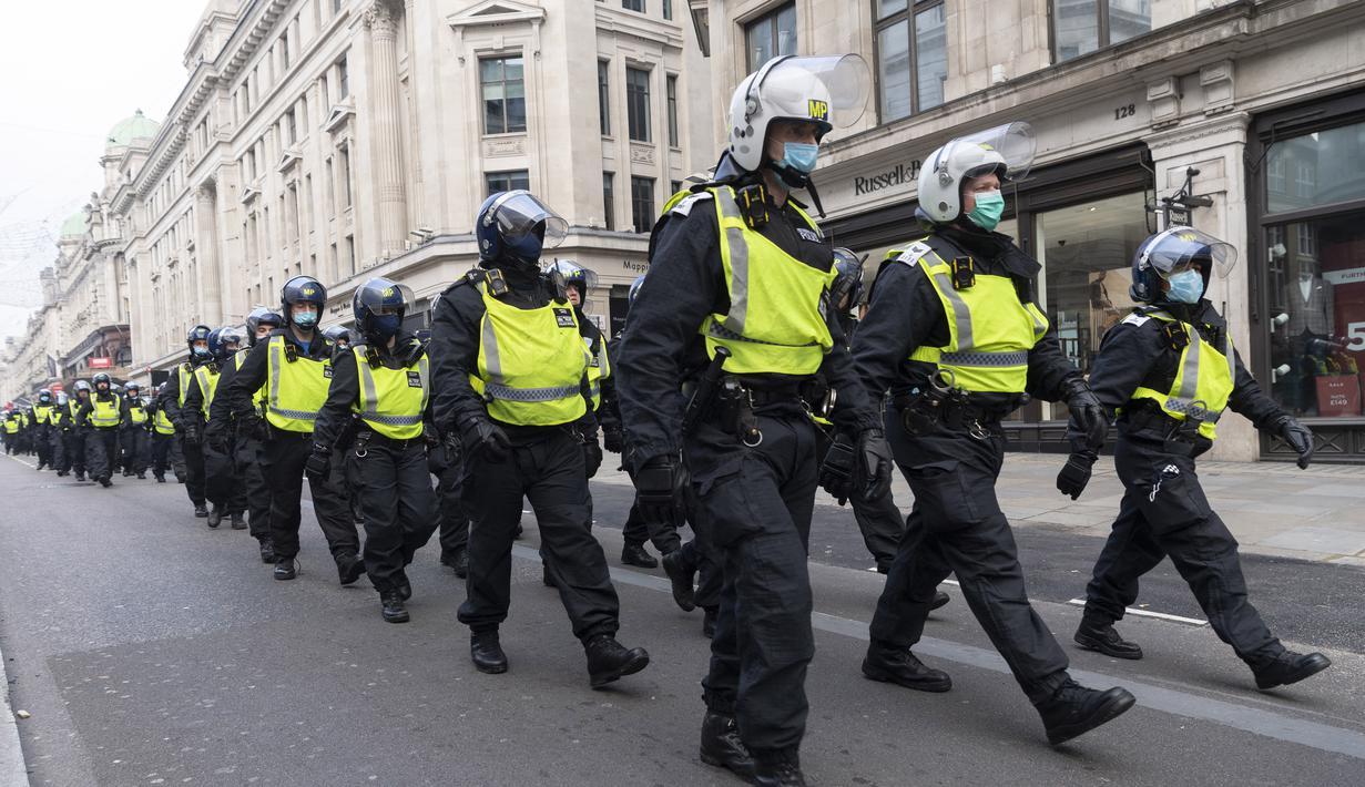 Para petugas polisi terlihat di sebuah jalan dalam aksi protes anti-lockdown di London, Inggris, 28 November 2020. Lebih dari 60 orang ditangkap saat bentrokan antara sejumlah demonstran anti-lockdown dan polisi di pusat kota London pada Sabtu (28/11). (Xinhua/Ray Tang)