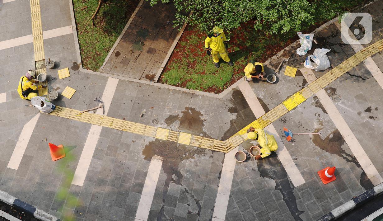 Pasukan Kuning dari Dinas Bina Marga memperbaiki garis kuning di trotoar kawasan Tanah Abang, Jakarta, Sabtu (22/5/2021). Garis kuning di trotoar yang dibuat khusus untuk jalur penyandang tunanetra tersebut diperbaiki agar nantinya dapat dilintasi dengan aman dan nyaman. (Liputan6.com/Angga Yuniar)