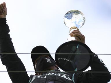 Pembalap Mercedes Lewis Hamilton merayakan kemenangannya pada F1 GP Eifel di Nuerburgring, Nuerburg, Jerman, Minggu (11/10/2020). Hamilton dengan 91 kemenangannya menyamai legenda F1 Michael Schumacher. (Bryn Lennon, Pool via AP)