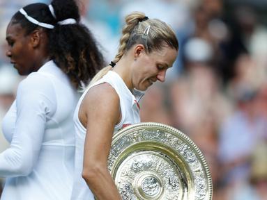 Petenis Jerman, Angelique Kerber (kanan) membawa trofi usai mengalahkan petenis AS, Serena Williams pada final tunggal putri kejuaraan Tenis Wimbledon 2018 di London, (14/7). Kerber menang atas Williams 6-3,6-3. (AP Photo/Nic Bothma)