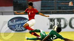 Bayu Gatra (4) melompat menghindari tackling keras pemain belakang Maladewa Mohamed Samdhooh (Liputan6.com/Helmi Fithriansyah)
