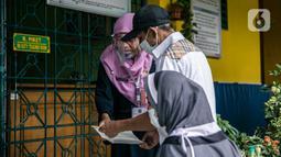 Warga berbincang dengan petugas saat mengambil Bantuan Sosial Tunai (BST) di SMAN 111, Jakarta, Selasa (19/1/2021). Pemprov DKI Jakarta menyalurkan BST sebesar Rp 300 ribu kepada 1.055.216 KK mulai Januari hingga April 2021. (Liputan6.com/Faizal Fanani)