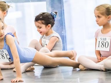 Penari balet cilik melakukan pemanasan sebelum mengikuti audisi di Sekolah Ballet Amerika (11/4/2016). Setiap anak berusia 6 sampai 10 tahun diundang untuk mengikuti audisi di Sekolah Balet Amerika. (AFP/Mark Sagliocco)