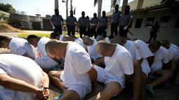 Anggota geng Mara Salvatrucha (MS-13) duduk berbaris di penjara dengan keamanan maksimal di Zacatecoluca, El Salvador (31/1). Anggota geng tersebut dipindahkan dari penjara kecil ke penjara keamanan maksimum. (AP Photo/Moises Castillo)