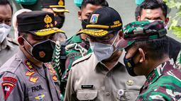 Pangdam Jaya Mayjen TNI Dudung Abdurrachman (kanan) dan Kapolda Metro Jaya Irjen Pol Fadil Imran (kiri) saat membagikan masker ke warga di Sunter Muara, Tanjung Priok, Jakarta, Selasa (9/2/2021). Kegiatan ini untuk menyadarkan masyarakat akan pentingnya penggunaan masker. (Liputan6.com/FaizalFanani)