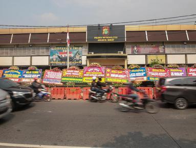 Kendaraan melintas di depan Polres Jakarta Barat yang dipenuhi karangan bunga, Jumat (23/11). Karangan bunga yang dikirimkan warga tersebut diberikan guna mendukung kepolisian dalam memberantas aksi premanisme di Jakbar. (Liputan6.com/Faizal Fanani)