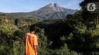 Seorang pria terlihat memantau aktivitas gunung merapi dari Lapangan Stiper, Glagaharjo, Cangkringan, Sleman, Kamis (19/11/2020). Status Gunung Merapi sudah dinaikkan pada 5 November 2020 lalu dari waspada level II menjadi siaga level III. (Liputan6.com/Johan Tallo)