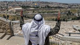 Seorang pria Palestina melaksanakan salat Jumat saat bulan Ramadan di depan Bukit Zaitun dengan latar belakang kota tua Yerusalem dan Masjid Al-Aqsa yang ditutup, Jumat (8/5/2020). Masjid Al-Aqsa telah ditutup sejak bulan lalu untuk mencegah penyebaran Covid-19. (Photo by AHMAD GHARABLI / AFP)