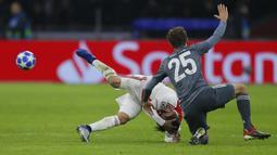 Bek Ajax Amsterdam, Nicolas Tagliafico, terjatuh usai ditendang gelandang Bayern Munchen, Thomas Mueller, pada laga Liga Champions di Johan Cruyff Arena, Amsterdam, Rabu (12/12). Kedua tim bermain imbang 3-3. (AP/Peter Dejong)