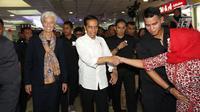 Seorang ibu bersamalan dengan Presiden Jokowi yang tengah mengajak Direktur Pelaksana IMF Christine Lagarde mengunjungi  Pasar Tanah Abang, Senin (26/2). Jokowi dan bos IMF langsung menuju lantai dua untuk mengitari Blok A. (Liputan6.com/Angga Yuniar)