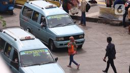 Warga berjalan di antara angkot yang menunggu di kawasan Stasiun Tanah Abang, Jakarta, Kamis (7/1/2021). Pemerintah akan melakukan pembatasan kapasitas dan operasional transportasi umum seiring diterapkannya kebijakan Pembatasan Kegiatan Masyarakat (PKM) di Jawa dan Bali. (Liputan6.com/Angga Yuniar)