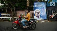Pengendara sepeda motor melintas di depan poster Rizieq Shihab di Jalan Petamburan 3, Jakarta, Rabu (30/12/2020). Pemerintah memutuskan untuk menghentikan kegiatan dan membubarkan organisasi massa Front Pembela Islam (FPI). (merdeka.com/Imam Buhori)