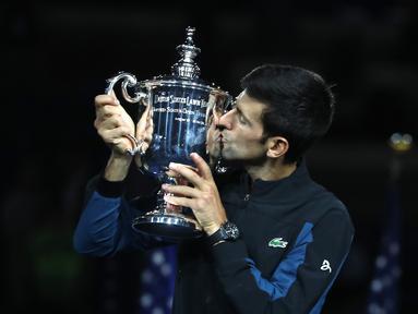 Petenis Serbia, Novak Djokovic mencium trofi turnamen AS Terbuka setelah mengalahkan Juan Martin del Potro dari Argentina pada partai final di New York, Minggu (9/9). Djokovic menang tiga set langsung 6-3, 7-6 (4), 6-3. (MATTHEW STOCKMAN/GETTY IMAGES/AFP)