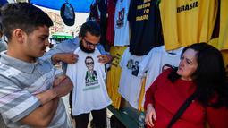 Pembeli memilih kaus bergambar Calon Presiden Brasil, Jair Bolsonaro dari sayap kanan dijajakan di sebuah toko pinggir jalan yang populer di Sao Paulo, 8 Oktober 2018. September lalu, Bolsonaro dirawat setelah ditusuk ketika kampanye. (AFP/NELSON ALMEIDA)