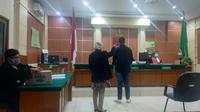 Terdakwa pembajakan film, Aditya Fernando Phasyah (AFP) saat disumpah sebelum disidang di PN Jambi.(Liputan6.com/Gresi Plasmanto)