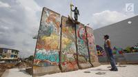 Seniman Teguh Ostenrik (kanan) mengawasi pemasangan pecahan Tembok Berlin dan Patung Menembus Batas di RPTRA Kalijodo, Jakarta, Selasa (26/9). Hal ini bertujuan agar masyarakat bisa melihat langsung tembok bersejarah itu. (Liputan6.com/Immanuel Antonius)