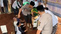 Kapolres dan Wakapolres Metro Tangerang, Kombes Harry Kurniawan dan AKBP Harley H. Silalahi, memakamkan santri korban kecelakaan lalu lintas (Liputan6.com/istimewa)