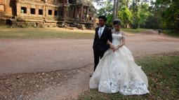 Sepasang pengantin baru melakukan foto pernikahan mereka di kompleks kuil Angkor Wat, sebuah candi ikonik dan bersejarah di Kamboja, 14 Maret 2018. Candi ini dibangun pada pertengahan abad ke-12 dan memakan waktu selama 30 tahun. (AP Photo/Heng Sinith)