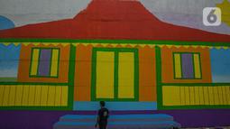 Pekerja melihat mural di Flyover Gaplek, Tangerang Selatan, Rabu (10/3/2021). Dengan mengangkat budaya lokal, simbol-simbol Betawi digambar menggunakan 1.200 Liter cat beragam warna. dan mural ditargetkan rampung pada akhir Maret 2021. (Liputan6.com/Faizal Fanani)