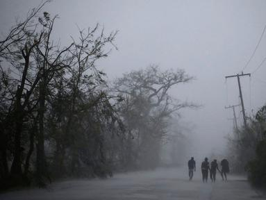 Warga berjalan di bawah tiang listrik setelah Badai Matthew menghantam wilayah Les Cayes di Haiti (4/10). Badai Matthew ini telah mengakibatkan banjir, banyak pohon tumbang dan ratusan rumah warga rusak parah. (REUTERS/Andres Martinez Casares)