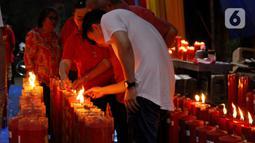 Warga keturunan Tionghoa menyalakan lilin saat melaksanakan sembahyang pada malam Tahun Baru Imlek 2571 di Vihara Dhanagun, Bogor, Jawa Barat, Jumat (24/1/2020). (merdeka.com/magang/Muhammad Fayyadh)