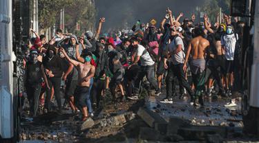 Demonstran saat bentrok dengan polisi di tengah pandemi virus corona Covid-19 selama penguncian wilayah (lockdown) di lingkungan miskin di Santiago, Chili, (18/5/2020). Mereka  protes menuntut bantuan makanan dari pemerintah. (AP Photo/Esteban Felix)