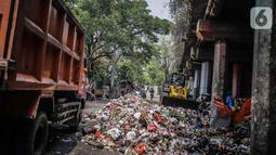 Petugas PPSU menggunakan kendaraan alat berat untuk mengangkut tumpukan sampah di kolong tol Wiyoto Wiyono, Tanjung Priok, Jakarta, Selasa (5/11/2019). Dalam sehari, petugas mengangkut sampah hingga 10 truk dengan berat total sekitar 100 ton ke TPA Bantar Gebang. (Liputan6.com/Faizal Fanani)