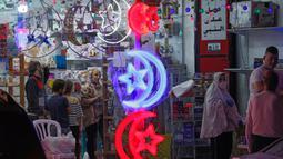 Orang-orang Palestina melihat toko yang menjual lampu hias ketika umat Muslim bersiap untuk memulai bulan suci Ramadan di Yerusalem timur, pada 21 April 2020. Beberapa jalanan di kota Yerusalem akan dihiasi dengan warna-warni lampu dan lentera untuk menyambut datangnya Ramadan. (Ahmad GHARABLI/AFP)