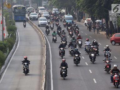 Pengendara sepeda motor melintasi jalur bus Transjakarta di Jalan Otista Raya, Jakarta, Rabu (11/7). Kurangnya pengawasan serta buruknya perilaku pengendara menyebabkan jalur tersebut sering diterobos kendaraan pribadi. (Liputan6.com/Immanuel Antonius)