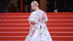 """Elle Fanning menaiki tangga karpet merah saat tiba menghadiri screening film """"Les Miserables"""" dalam acara Festival Film Cannes ke-72 di Prancis (15/5/2019). Aktris 21 tahun ini tampil cantik mengenakan gaun taman haute couture karya Valentino. (AP Photo/Arthur Mola)"""