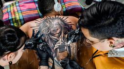 Seniman membuat tato di tubuh seorang pria saat acara Expotattoo Colombia 2019 di Medellin, departemen Antioquia (2/6/2019). Para penggila tato antusias untuk mentato tubuhnya di festival tato terbesar di negara tersebut. (AFP Photo/Joaquim Sarmiento)