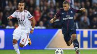 Penyerang PSG, Kylian Mbappe membawa bola dari kejaran gelandang Bayern Munchen Thiago Alcantara saat bertanding pada grup B Liga Champions di stadion Parc des Princes di Paris, Prancis (27/9). PSG menang telak 3-0 atas Munchen. (AFP Photo/Franck Fife)